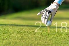 Golfspeler Aziatische vrouw die golfbal zetten voor Gelukkig Nieuwjaar 2018 op het groene golf, exemplaarruimte Stock Foto