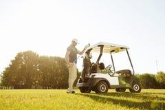 Golfspeler die clubs van een zak in een golfkar nemen Stock Foto