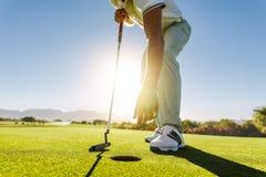 Golfspeler die de bal van gat na gezet plukken stock afbeeldingen
