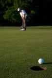 Golfspeler die een golfbal zet Stock Fotografie