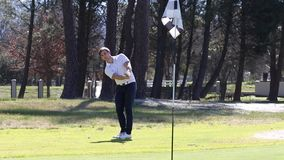 Golfspeler die een spaander raken stock footage