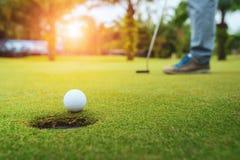 Golfspeler die golfbal op het groene golf, lensgloed op tijd van de zon de vastgestelde avond, Progolf lange het zetten golfbal a stock fotografie