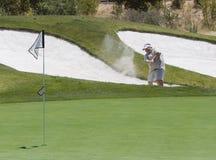 Golfspeler die uit Bunker raakt Stock Fotografie