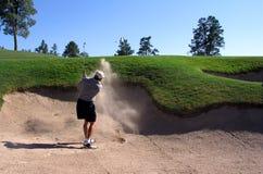 Golfspeler die uit een bunker raakt Stock Foto