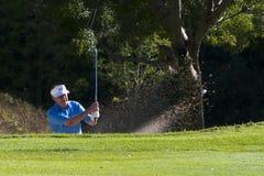 Golfspeler die van bunker raakt Stock Fotografie