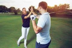 Golfspeler die van het spel op gebied genieten en handen schudden stock afbeeldingen