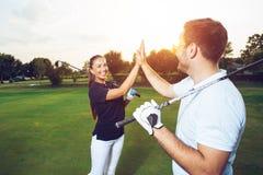Golfspeler die van het spel op gebied genieten en handen schudden stock fotografie