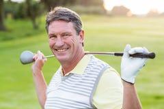 Golfspeler die zich en zijn club bevinden slingeren die bij camera glimlachen Stock Foto
