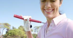 Golfspeler dragende golfclub over schouder terwijl het gebruiken van mobiele telefoon stock footage