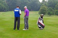 Golfspeler en theebus die een cursusgids lezen Stock Foto