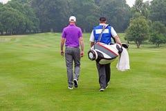 Golfspeler en theebus die omhoog fairway lopen Stock Foto's