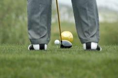 Golfspeler om aan de slag van bal voorbereidingen te treffen Stock Afbeelding