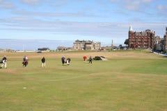 Golfspelers die aan het Huis van de Club lopen Stock Fotografie