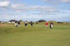 Golfspelers die over golfcursus lopen Stock Foto's