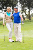 Golfspelpar som ler på de på den sättande gräsplanen Royaltyfri Bild