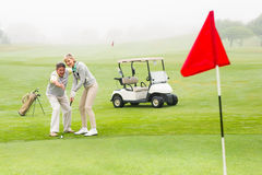 Golfspelpar som tillsammans sätter bollen Royaltyfria Foton