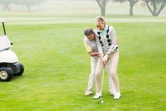 Golfspelpar som tillsammans sätter bollen Arkivbilder