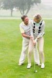 Golfspelpar som tillsammans sätter bollen Royaltyfri Bild