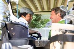 Golfspelvänner som kör i deras golfbarnvagn som till varandra ler Arkivfoton