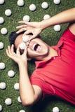 Golfspieler auf Fußboden mit Kugeln auf Augen. Lizenzfreies Stockfoto