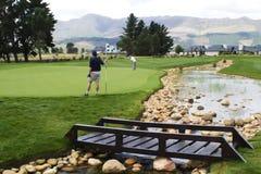 Golfspieler auf Grün mit Brücke Lizenzfreies Stockfoto
