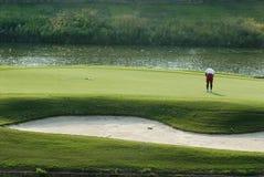 Golfspieler auf setzendem Grün Stockbild