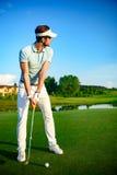 Golfspieler auf setzendem Grün stockfotografie