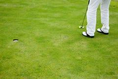 Golfspieler auf setzendem Grün Stockfoto