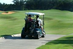 Golfspieler auf Wagen. Lizenzfreie Stockbilder