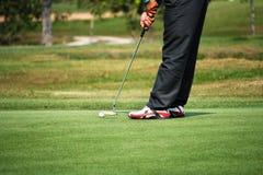 Golfspieler, der auf das Grün sich setzt Stockfotografie