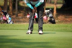 Golfspieler, der auf das Grün sich setzt Lizenzfreies Stockbild