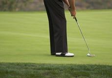 Golfspieler, der auf das Grün sich setzt Lizenzfreies Stockfoto