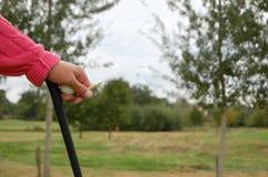 Golfspieler, der auf seinem Klumpen, mit einem Golfball und einem T-Stück in seiner Hand sich lehnt Lizenzfreies Stockbild