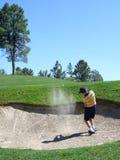 Golfspieler, der aus einem Sandfang heraus schlägt stockfotografie