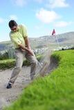 Golfspieler, der aus einem Sandfang heraus spielt Stockbilder