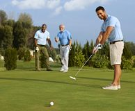 Golfspieler, der Ball auf Grün setzt Lizenzfreie Stockfotografie