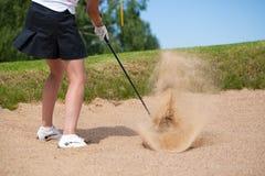 Golfspieler, der ein T-Stück geschossen im Sand schlägt stockfotos