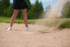 Golfspieler, der ein T-Stück geschossen im Sand schlägt stockfoto