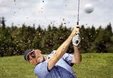 Golfspieler, der einen Golfball schießt stockfoto