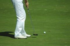 Golfspieler, der einen Golfball setzt Stockfotografie