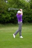 Golfspieler, der einen mittleren Eisenschuß spielt Stockbilder