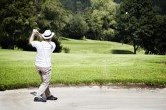 Golfspieler, der im Bunker abbricht. Lizenzfreies Stockfoto