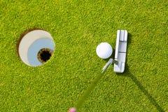 Golfspieler, der Kugel in Loch einsetzt Stockfotos