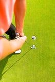 Golfspieler, der Kugel in Loch einsetzt Lizenzfreies Stockbild