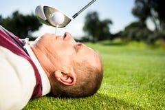 Golfspieler, der T-Stück in seinen Zähnen hält Stockbilder