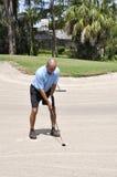 Golfspieler, der von einem Sandfang sich setzt Lizenzfreie Stockfotografie