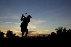 Golfspieler, der weg am Sonnenuntergang abzweigt Lizenzfreies Stockfoto