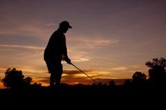 Golfspieler, der weg am Sonnenuntergang abzweigt Stockbild