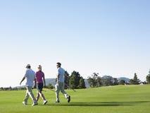 Golfspieler, die auf Golfplatz gehen Stockbild