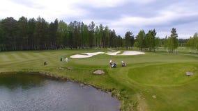 Golfspieler, die Golfschuß mit Verein auf Kurs während auf den Sommerferien, von der Luft schlagen stockfotografie